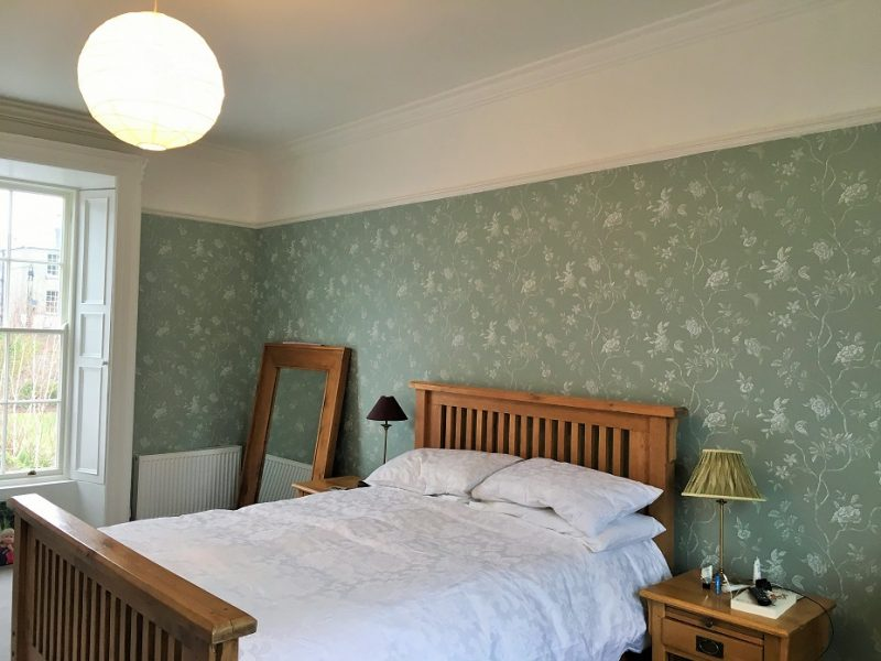 After photo of a master bedroom in a period house that was wallpapered and redecorated by Impressions Painting and Decorating